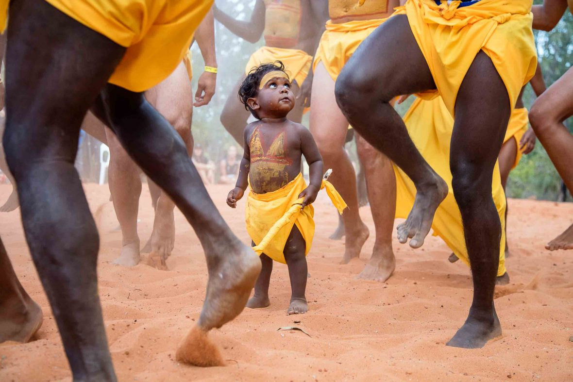 A toddler looks up among a sea of legs during a ceremonial dance.