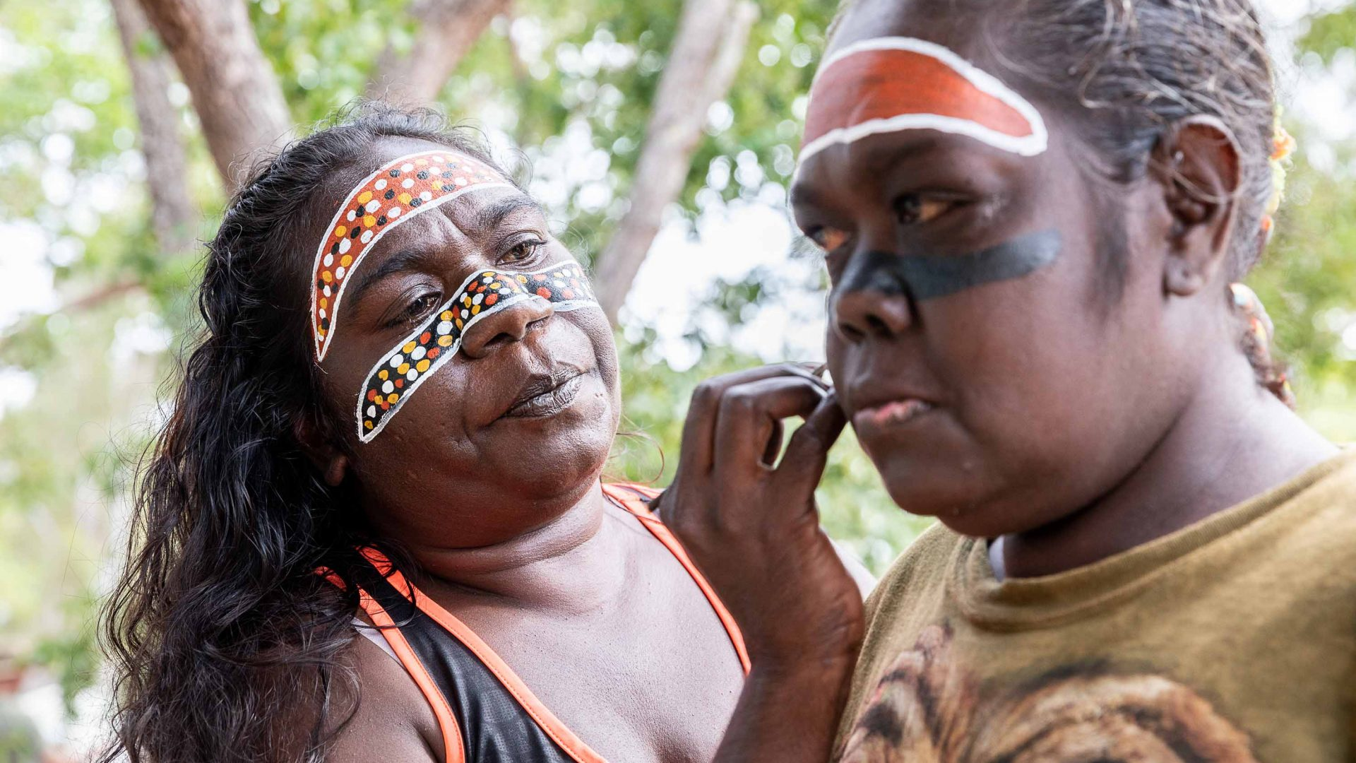 A woman paints the face of another woman.