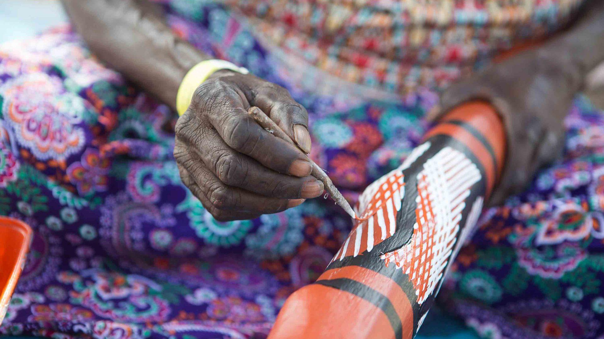 Hands painting a didgeridoo.