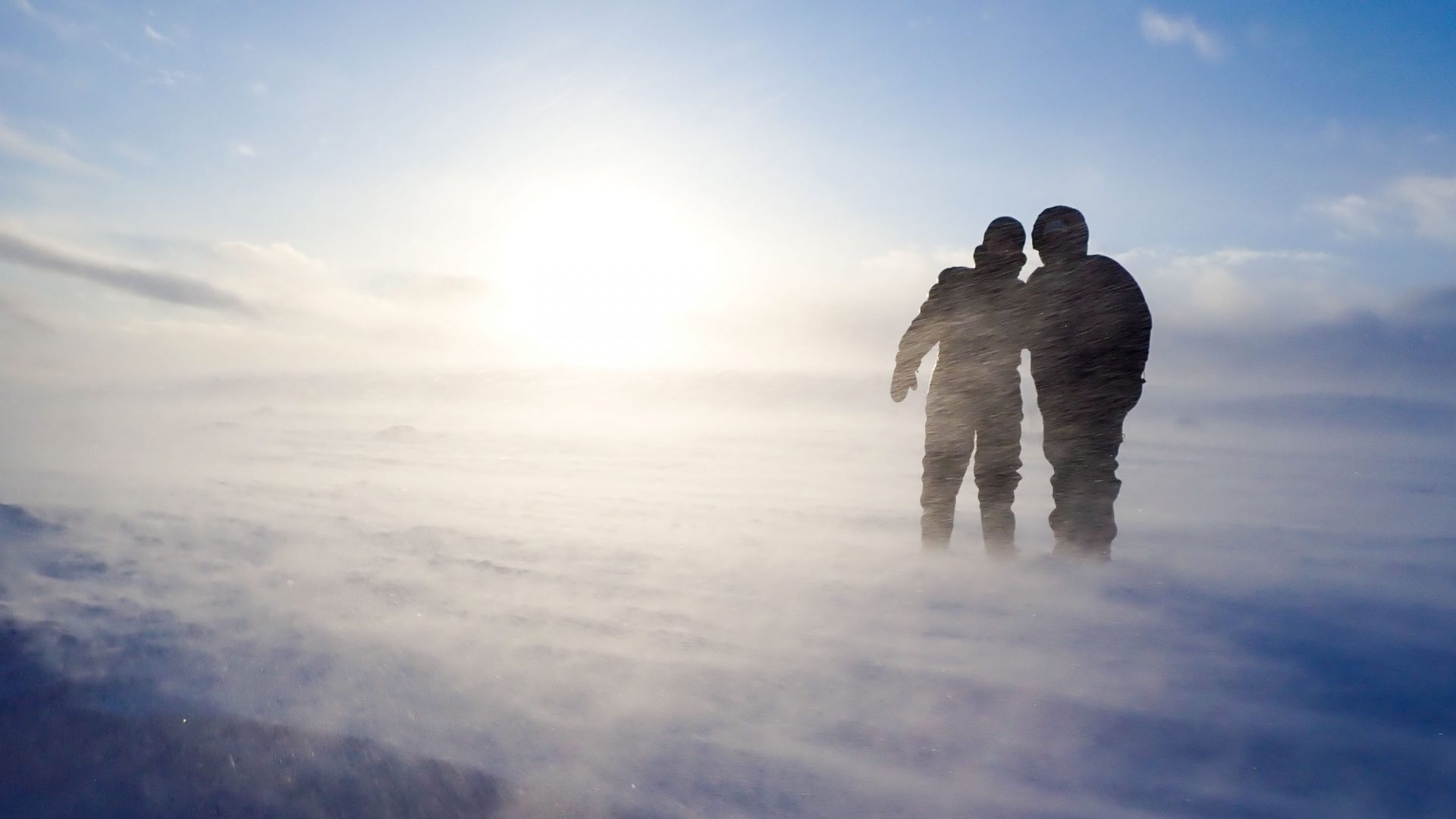 Two friends are silhouetted in the snow.