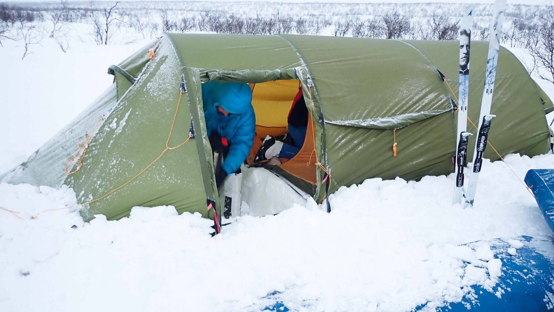 A tent buried in snow.