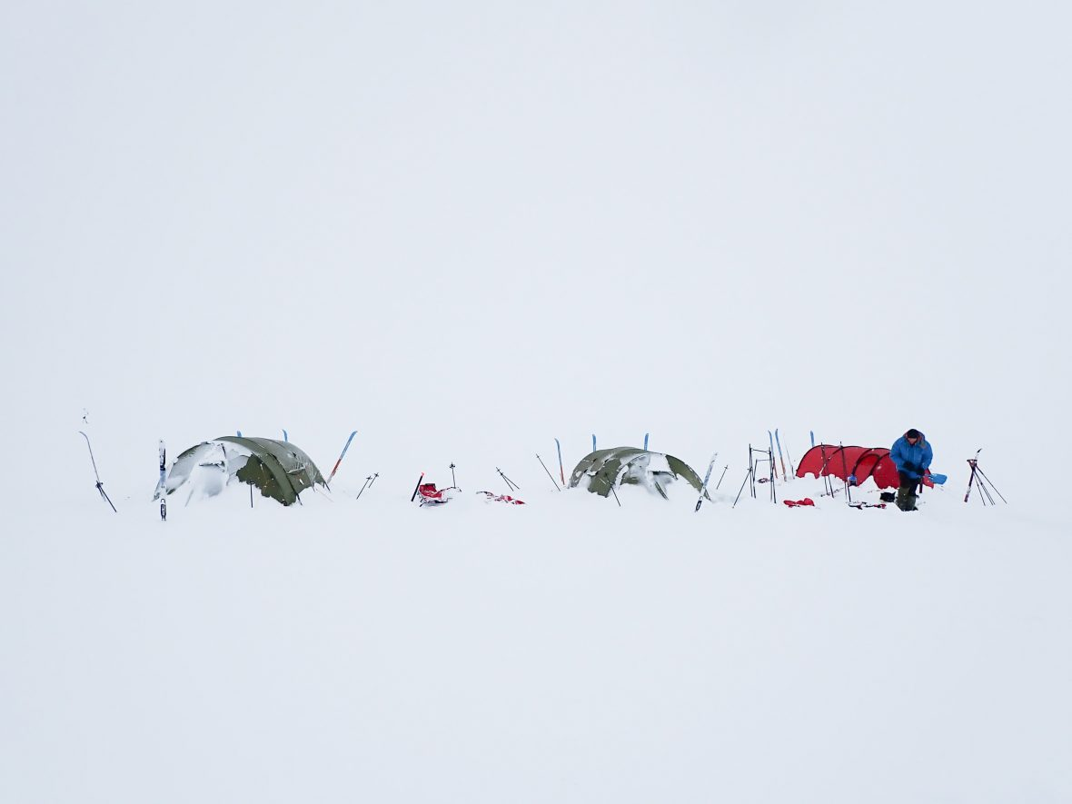 A row of tents buried in the snow.