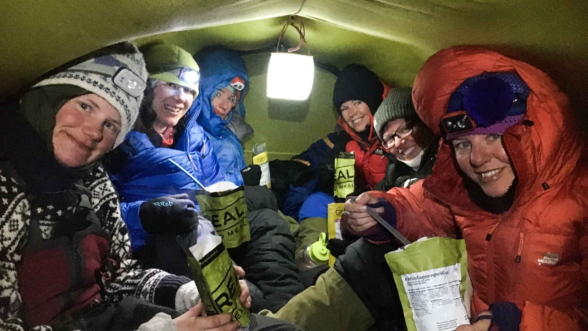 Friends crammed together into a tent.