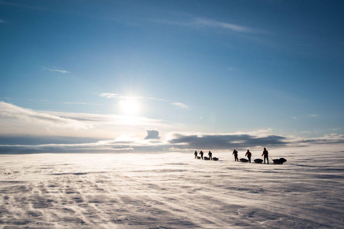 Skiers crossing the vast plains.