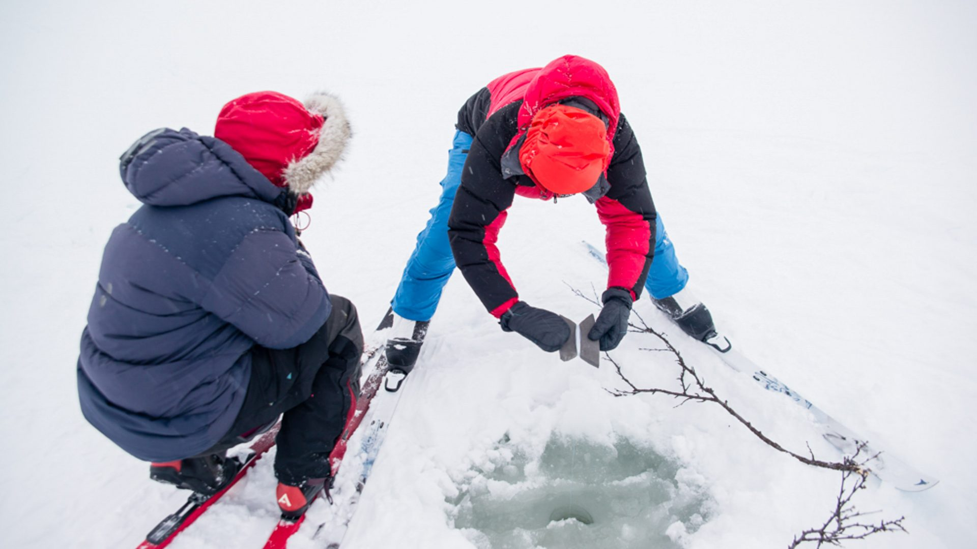 Two friends dig out water from a hole in the snow.
