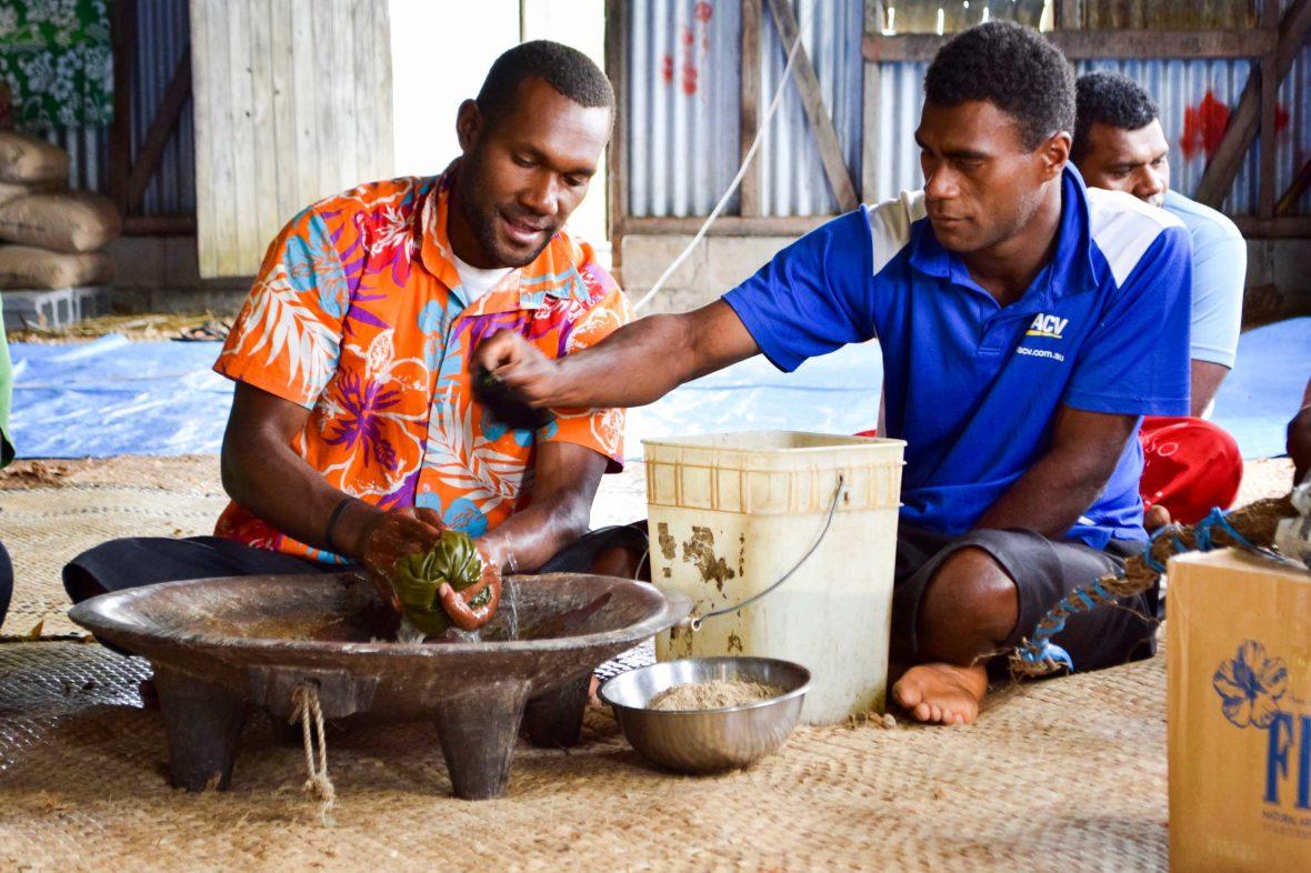 Two men prepare kava in Naga village.