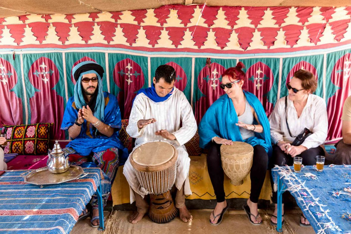 Travelers play traditional drums.
