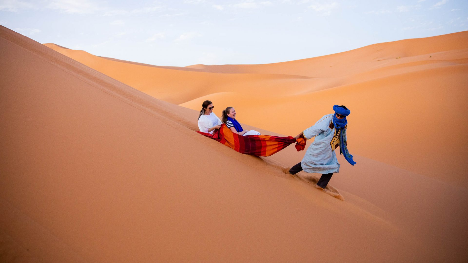 Someone pulling travelers on a rug down a dune in the Sahara.