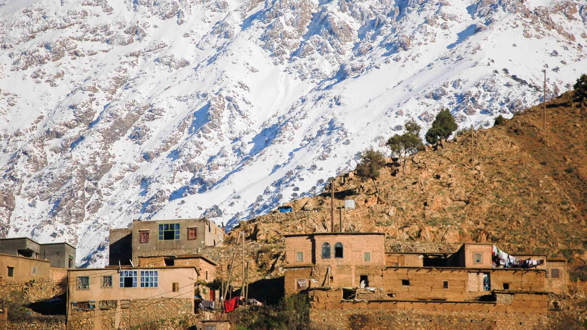 A Berber village in front of snowy mountains.