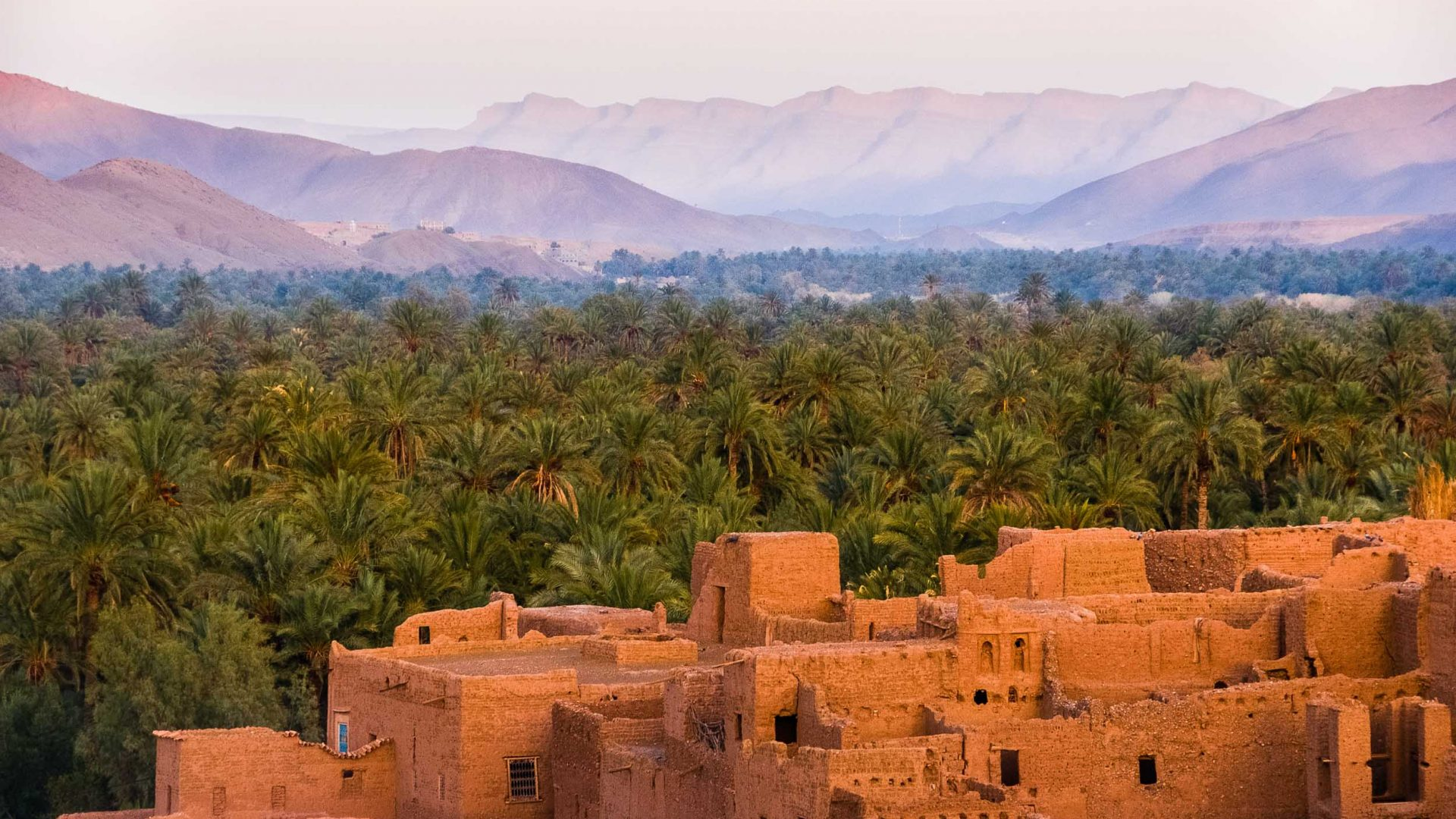 Mud-colored houses against a backdrop of mountains in Tamnougalt, Morocco.
