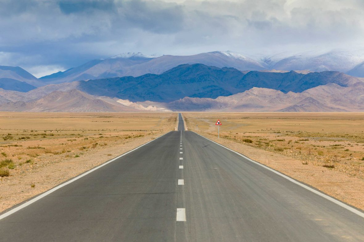 A road leads to barren mountains.
