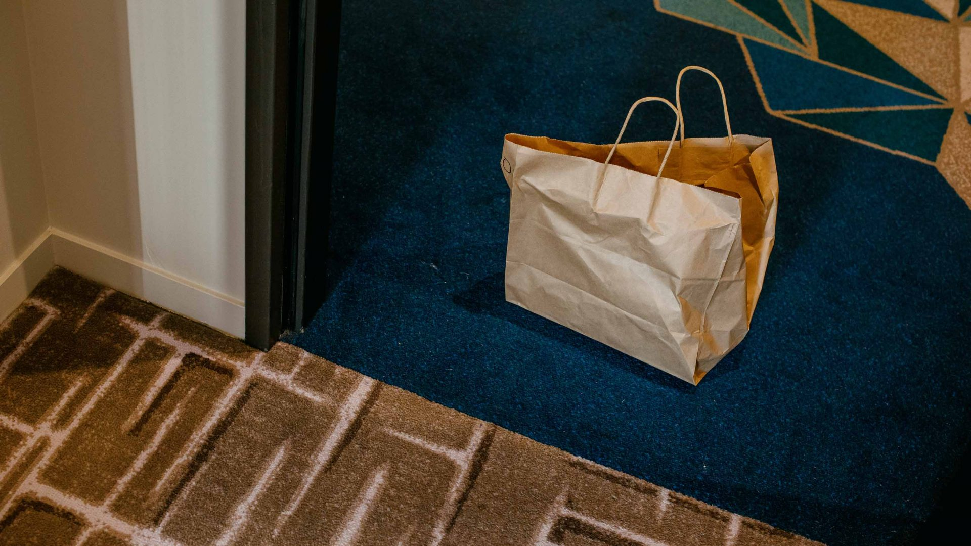 A paper bag at the door of the hotel room.