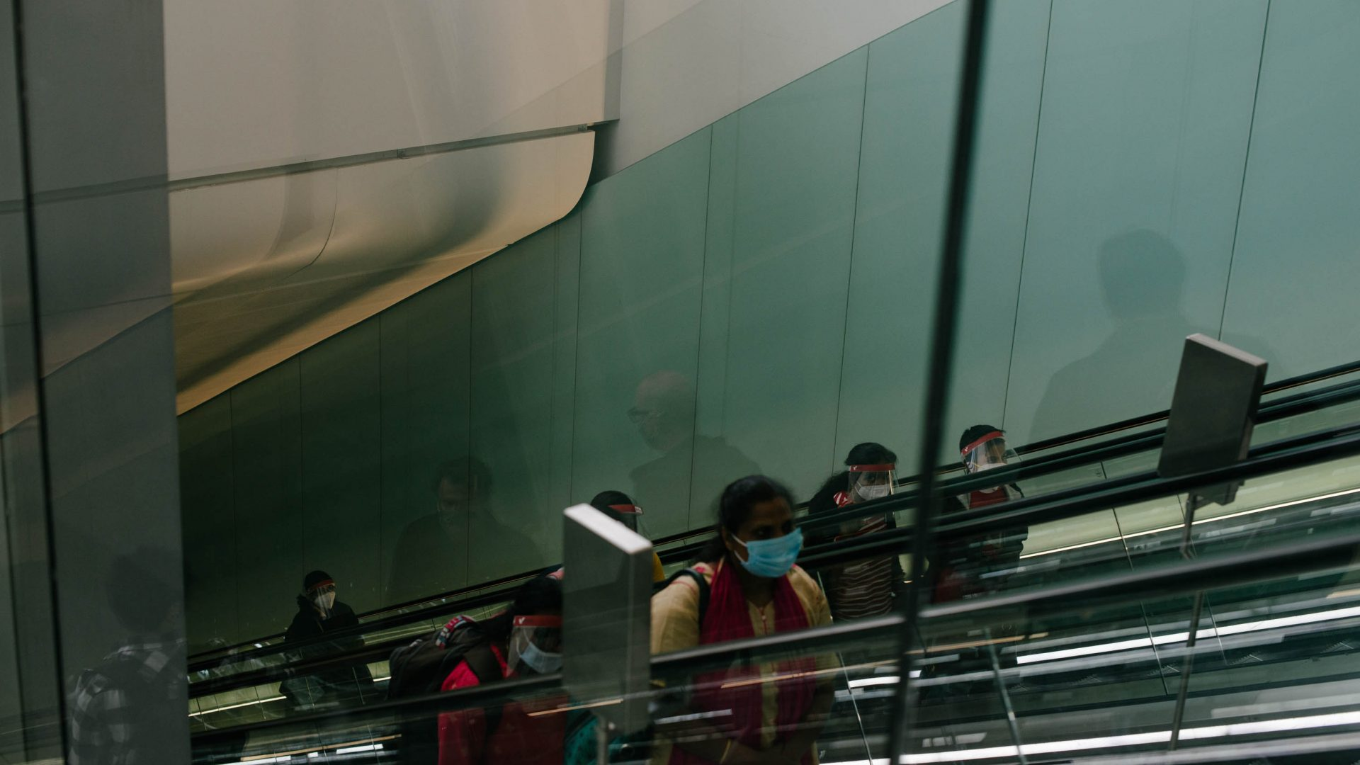 People at the airport on an escalator wearing masks.