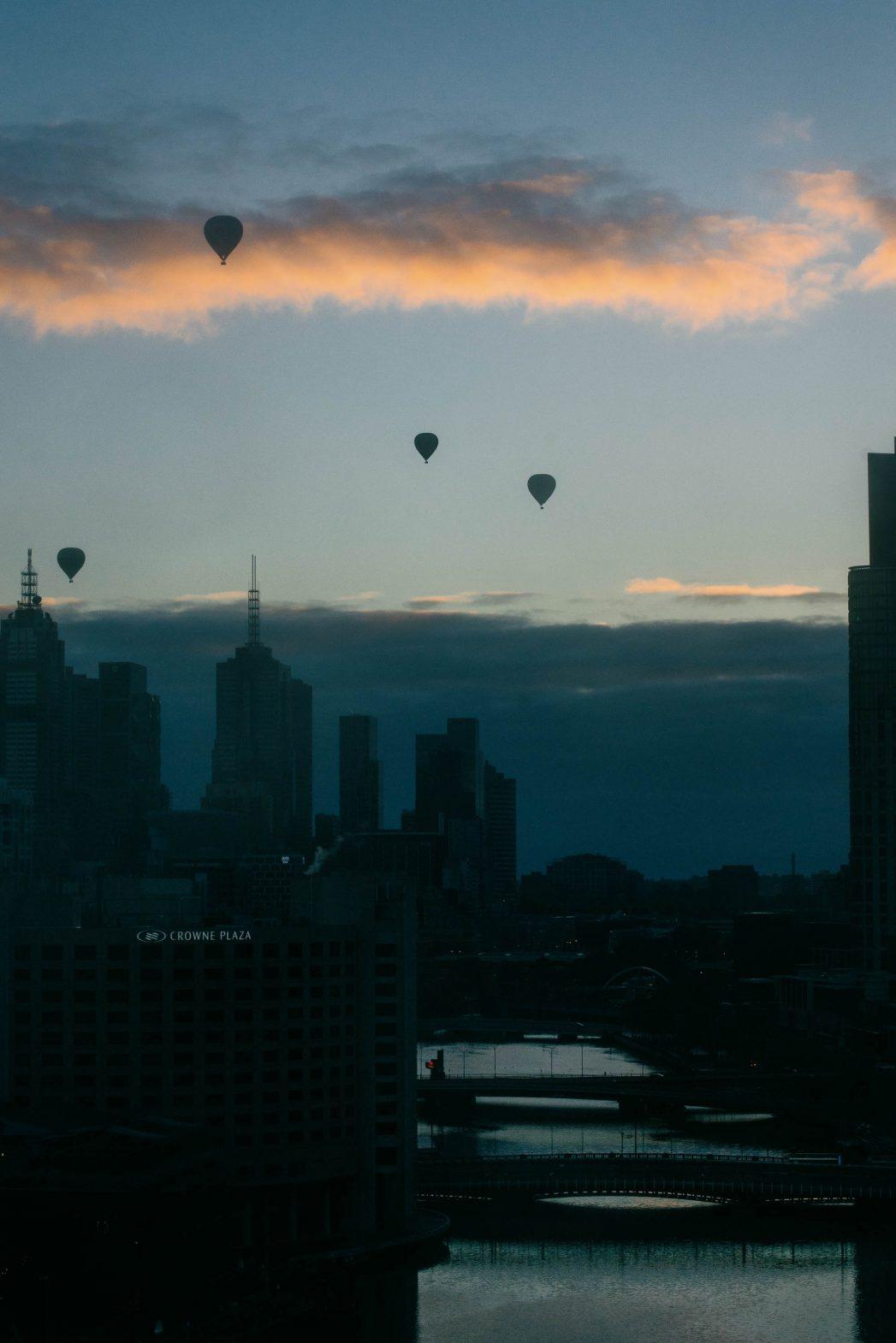 hot air balloons over the city skyline.