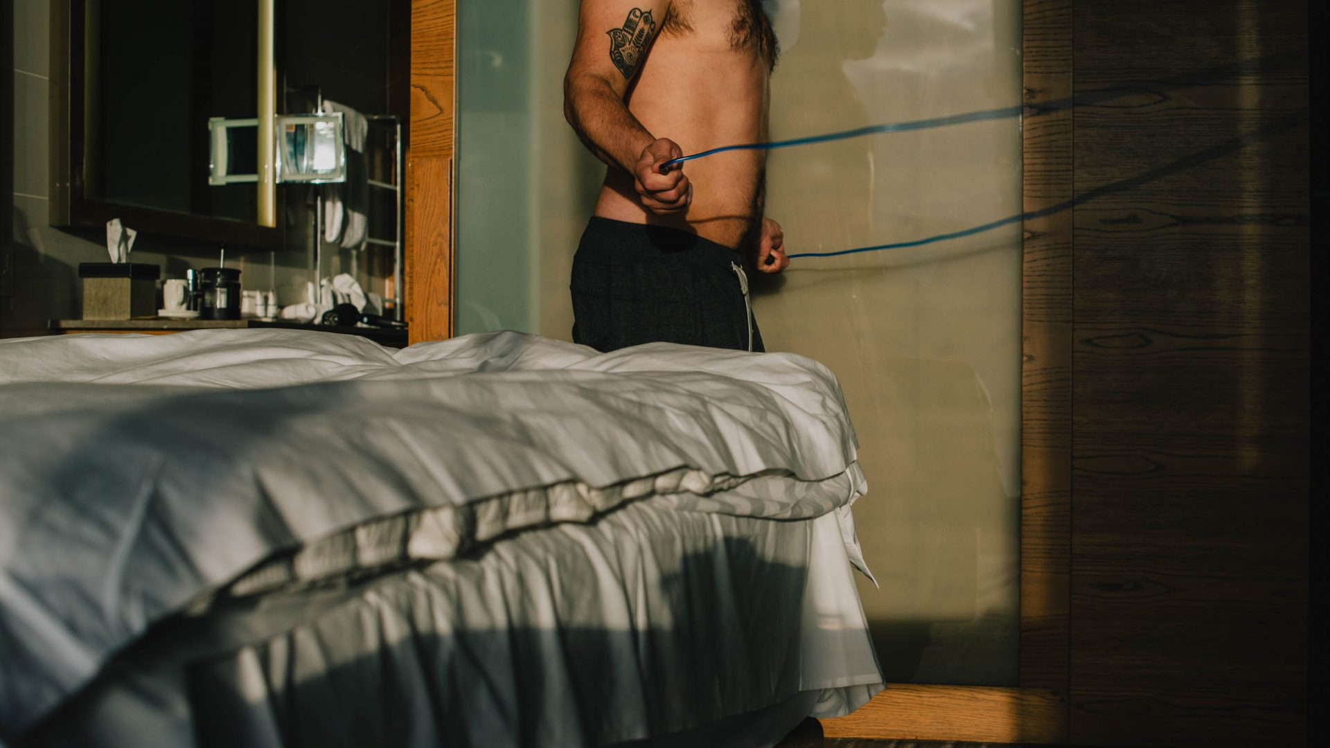 A mans body is seen exercising next to a bed.