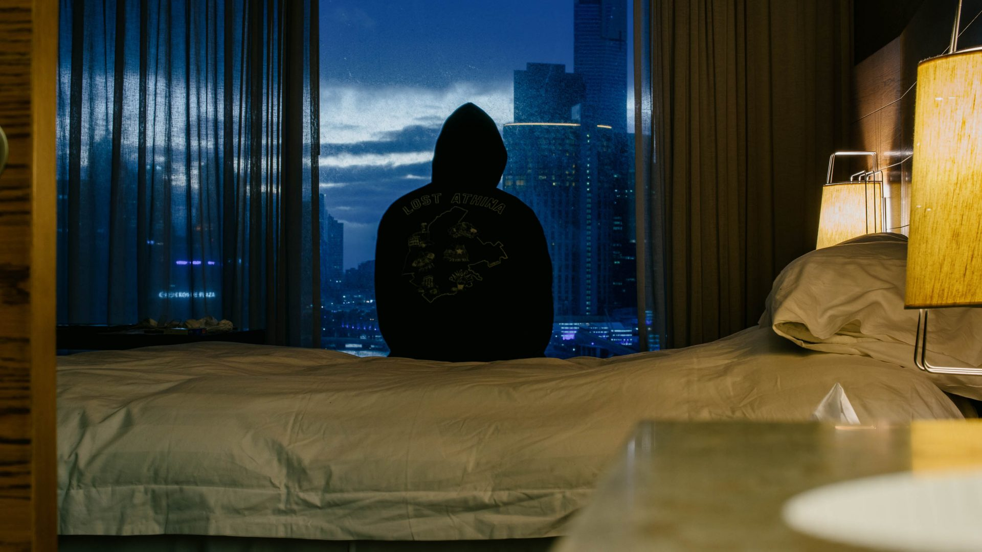 Silhouette wearing a hood against the window.