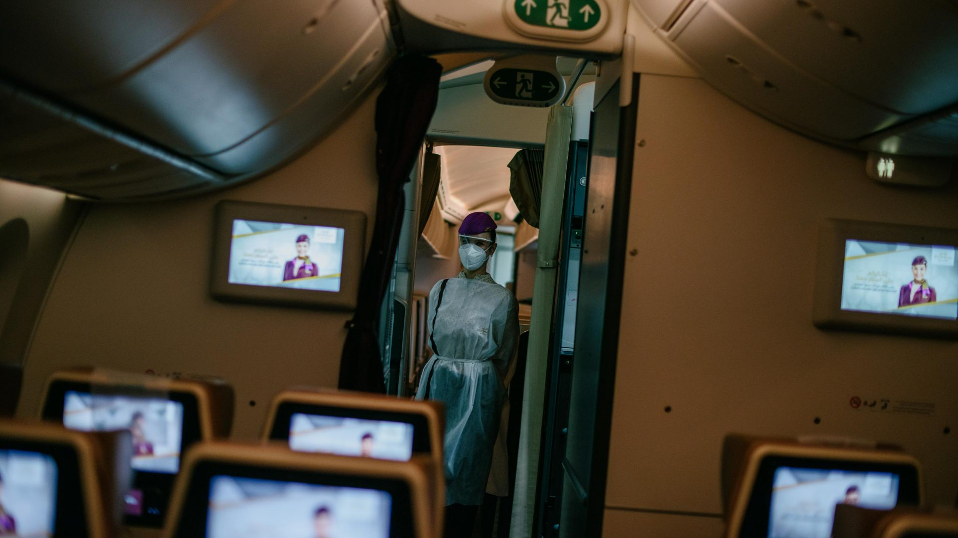 Screens on a largely empty aircraft with cabin crew in PPE.