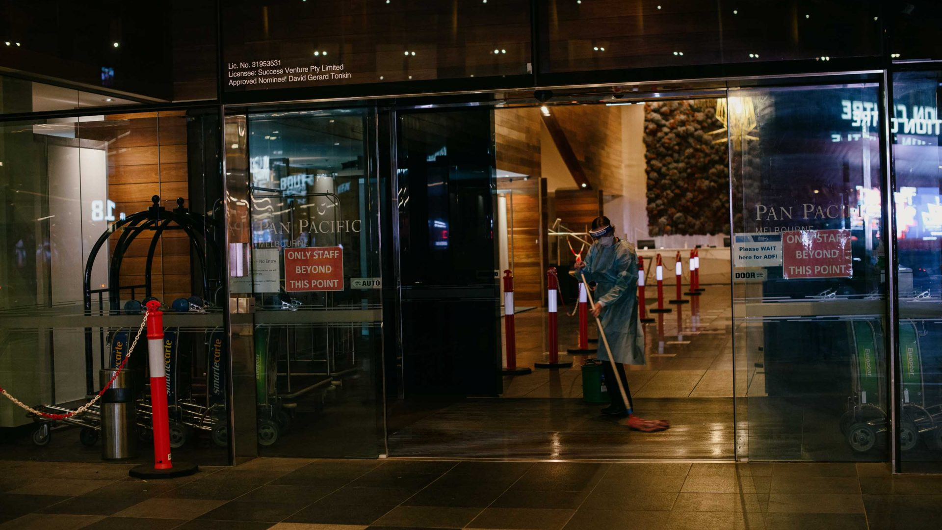 Cleaners clean the entry way of the hotel.
