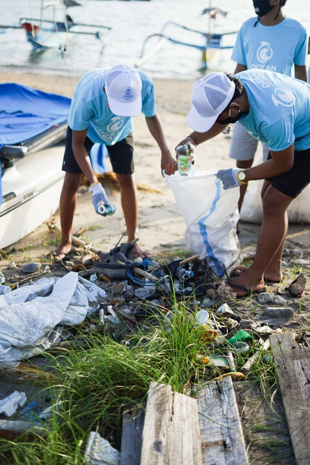 People collect plastic waste from a beach